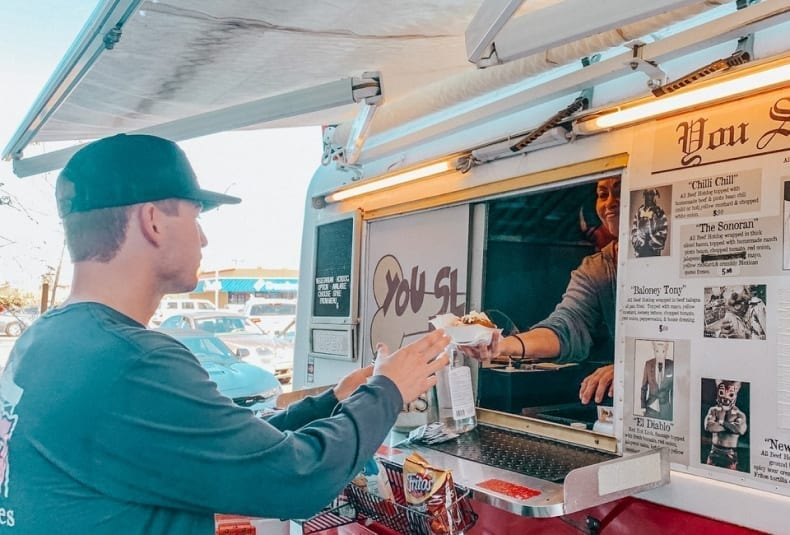 Man receiving hot dog from food truck